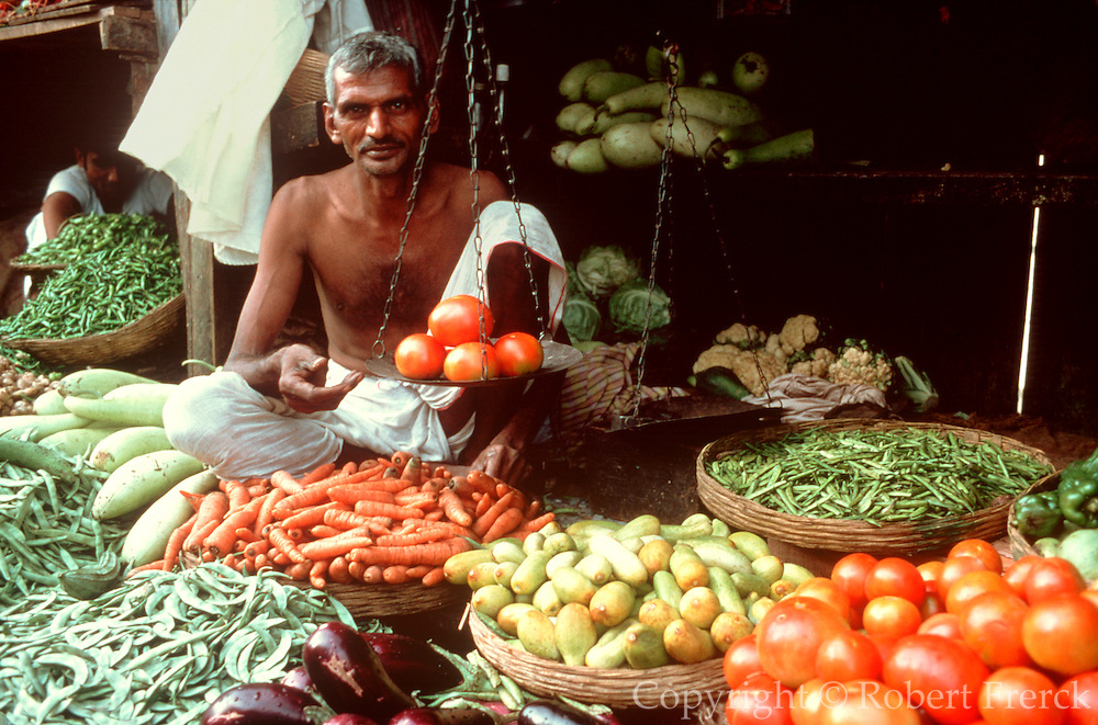 INDIA, MARKETS vendor selling vegetables in a  produce market in Bombay
