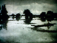 Dreamlike picture of a tiny boat sailing on waters in a flooded area. Laos, Asia. Pictures is completely out of focus.