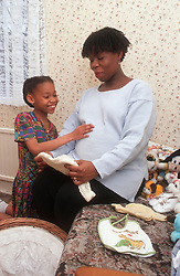 Young girl feeling pregnant mother's stomach,