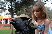 """Child (6 years old) sharing her hat with  """"Curtain Call"""" sculpture by Les Kossatz. Darling Harbour, Sydney, Australia"""