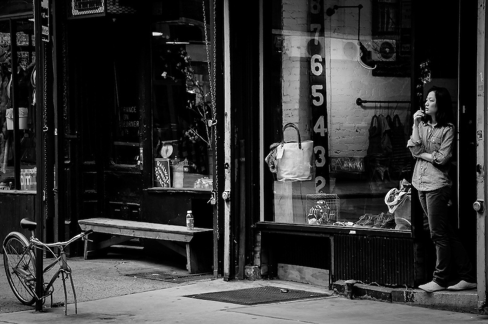 A girl working at a store in the Lower East Side of Manhattan smokes a cigarette at the store doorstep, Manhattan, New York, 2010.