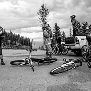 Riders prep their bikes to drop into the Fuzzy Bunny Trail off of Teton Pass near Wilson, Wyoming.