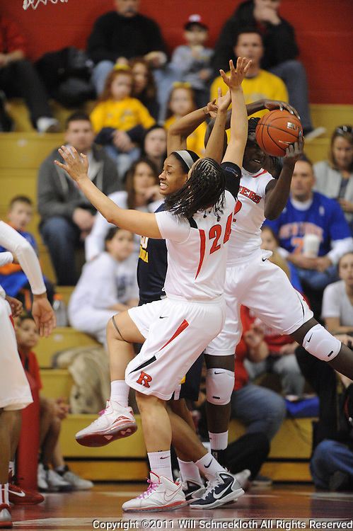 Rutgers Scarlet Knights guard/forward April Sykes (24) and forward Chelsey Lee (52) beat West Virginia Mountaineers center Asya Bussie (20) for a rebound during first half Big East NCAA women's basketball action between Rutgers and West Virginia at the Louis Brown Rutgers Athletic Center