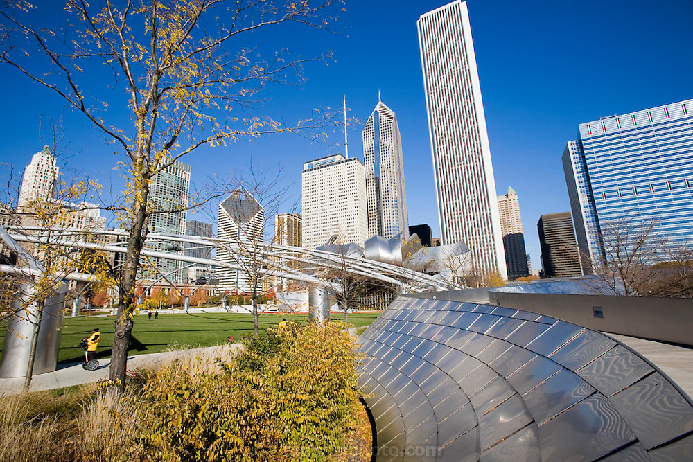 A Segway motorized transport rider passes between the Frank Gehry-designed BP Bridge and the trellis of the Jay Pritzker Pavilion, also designed by Gehry in Millennium Park, Chicago, Il. USA. And downtown cityscape.