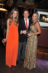 Left to right, KATIE READMAN, HARRY BECHER and DAVINA HARBORD at the Wild for WSPA dinner in aid of the charity World Society for the Protection of Animals held at Under The Bridge, Stamford Bridge, Fulham Road, London on 23rd February 2012.