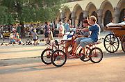 Friends age 21 riding double bicycle through city center.  Krakow Poland