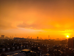 © London News Pictures. London. UK. 31/01/2014. <br /> A bright orange sunrise over the London skyline on a January winters morning. Showing famous landmarks on the horizon including the The Shard and Westminster Abbey. Photo credit: Brad Straughan/LNP