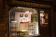 Antiques in window display at antique shop along Burford High Street at night, The Cotswolds