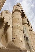 Tall Colossi in the Court of Ramesses II at the ancient Egyptian Luxor Temple, Nile Valley, Egypt. The temple was built by Amenhotep III, completed by Tutankhamun then added to by Rameses II. Towards the rear is a granite shrine dedicated to Alexander the Great  and in another part, was a Roman encampment. The temple has been in almost continuous use as a place of worship right up to the present day.