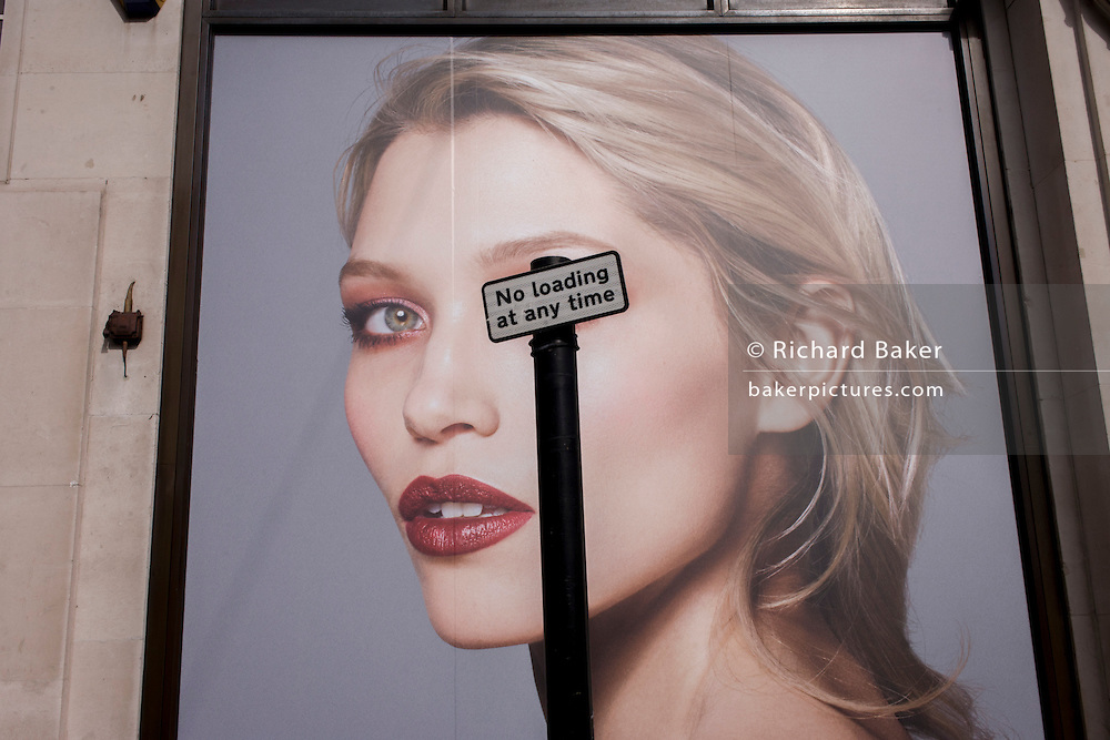 A No Loading parking sign obscures the right eye of a female model outside a fashion retailer in Oxford Street, central London.