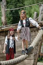Two girls dressed as pirates playing on a adventure playground, Bavaria, Germany