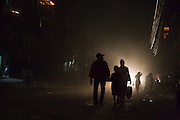 A family, backlit by car headlights, walks down a dusty street in Boudhanath, Kathmandu, Nepal.