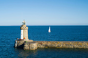 Yacht sailing past Guernsey island lighthouse and breakwater pier, St Peter Port, Channel Isles
