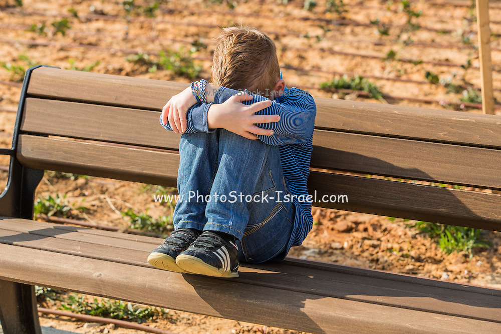Young depressed red haired boy alone on a bench in a park