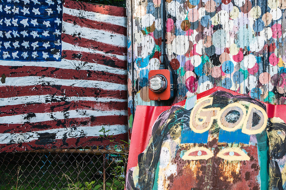 "American flag and ""God"" painted hood, Heidelberg Project, Detroit, Michigan.  The Heidelberg Project is a grass roots project started by artist Tyree Guyton that uses art to help revitalize the embattled neighborhood.  Each year, over 275,000 people visit the project .  For more information, go to www.heidelberg.org"