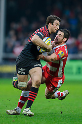 Saracens Outside Centre (#13) Marcelo Bosch is tackled by Gloucester Flanker (#6) Matt Cox during the first half of the match - Photo mandatory by-line: Rogan Thomson/JMP - Tel: Mobile: 07966 386802 - 04/01/2014 - SPORT - RUGBY UNION - Kingsholm Stadium, Gloucester - Gloucester Rugby v Saracens - Aviva Premiership.