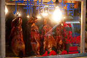 Crispy Peking Duck hangs in the window of a Chinese restaurant in Shanghai, China. These ducks have been covered in spices and deep fried to give them a glistening and crispy skin, a speciality of Chinese cooking.