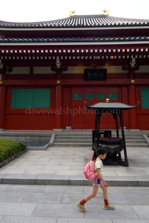 Girl passes shrine at Asakusa Kannan Temple Gardens Tokyo, Japan