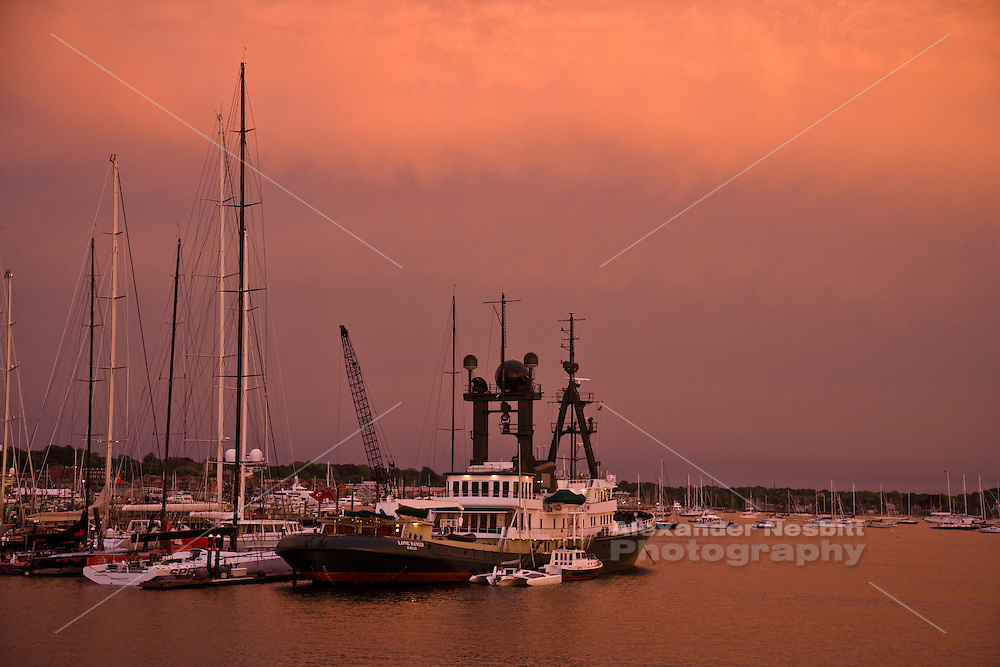 A hazy sunset illuminates Newport harbor and the American Shipyard with an unusually dramatic orange glow.
