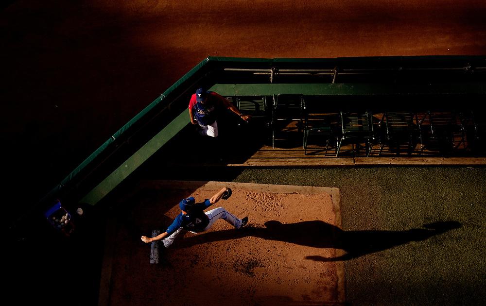 Matt Harrison throws in the bullpen as bullpen coach Andy Hawkins watches. Photographed at Rangers Ballpark in Arlington, Texas.