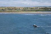 Views from the coastal path out to sea as a small fishing boat skips over a wave while leaving Parrog on 17th August 2021 in Newport, Pembrokeshire, Wales, United Kingdom. Newport is a town, parish, community, electoral ward and ancient port of Parrog, on the Pembrokeshire coast in West Wales at the mouth of the River Nevern in the Pembrokeshire Coast National Park.