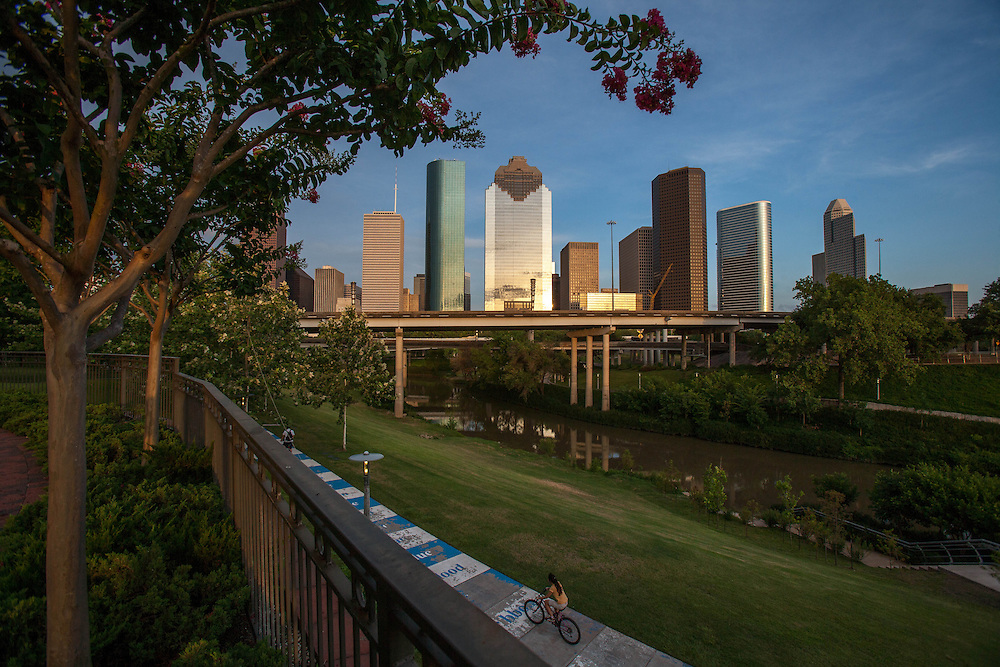 Houston, Texas skyline from Buffalo Bayou with people bicycling along path.