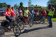 A tour guide gives a talk about electric bikes to a group of people who will be taking the bikes on a tour from the UK Electric Bike Centre, Staplehurst, Kent, England, UK.