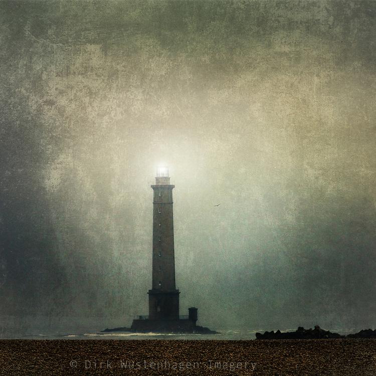 Famous lighthouse Phare du Cape de la Hague, Normandy, France on a very misty summer day.