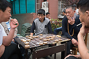 Farmers who sold their land to the government. Some sold their land for the equivalent of 1 million euros or more. They had no choice but to sell their land. Now theu play Chinese chess and live the apartment blocks above, they were given places to live. A real life changer for them<br /><br />Huge construction and recently built tower blocks in Tongzhou city on the outskirts of Beijing. All the old buildings, villages have been destroyed to make way for the mega cities of today