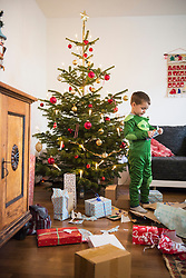 Young boy opening Christmas gift at home