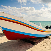 A brightly painted boat pulled up on the sandy beach at Playa del Carmen on Mexico's Yucatan Peninsula with partly cloudy sky in the background.