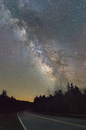 The West Virginia Highlands Scenic Highway is devoid of travelers at night; the road, the sentinel pines, the Milky Way above, and the hooting owls are this night's only companions.