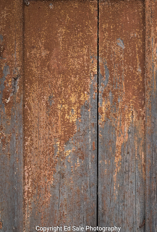 Colorful brownish-yellow weathered paint slowly deteriorates from a wooden door in Tuscany.