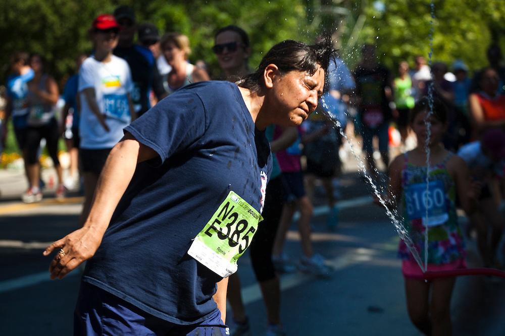 Veronica Giustino puts her face into a jet of water running in the 2012 Bolder Boulder 10K road race in Boulder, Colorado.
