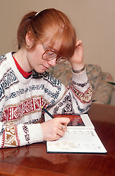 Teenage girl sitting at desk writing notes in diary,