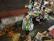 04 JANUARY 2016 - BANGKOK, THAILAND: A shopper in Bang Chak Market watches as shops are closed in the market. The market closed January 4, 2016. The Bang Chak Market serves the community around Sois 91-97 on Sukhumvit Road in the Bangkok suburbs. About half of the market has been torn down. Bangkok city authorities put up notices in late November that the market would be closed by January 1, 2016 and redevelopment would start shortly after that. Market vendors said condominiums are being built on the land.          PHOTO BY JACK KURTZ