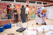 08/09/2015 - Lisbon, Portugal:Olinda Rodrigues, 66, looks for a different stencil, while other participants of Lata 65 paint the wall. Lata 65 was project created by Lara Seixo Rodrigues and is a creative workshop teaching street art to senior citizens. (Eduardo Leal)