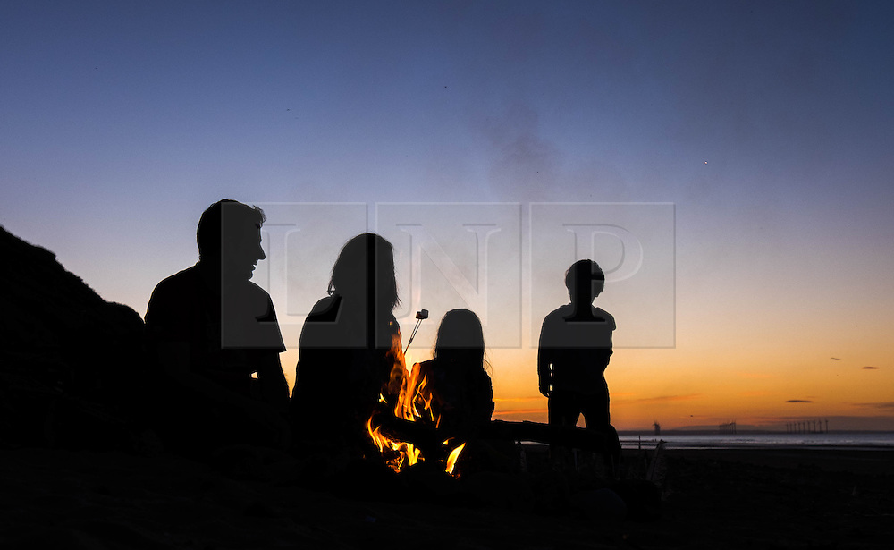 © Licensed to London News Pictures.27/08/15<br /> Saltburn, UK. <br /> <br /> NEIL WHITTLE and his wife Jenny from Saltburn sit with their daughter Mia, 6, and son, Rohan, 3, as they eat marshmallows roasted over a fire on the beach at sunset.<br /> <br /> Photo credit : Ian Forsyth/LNP