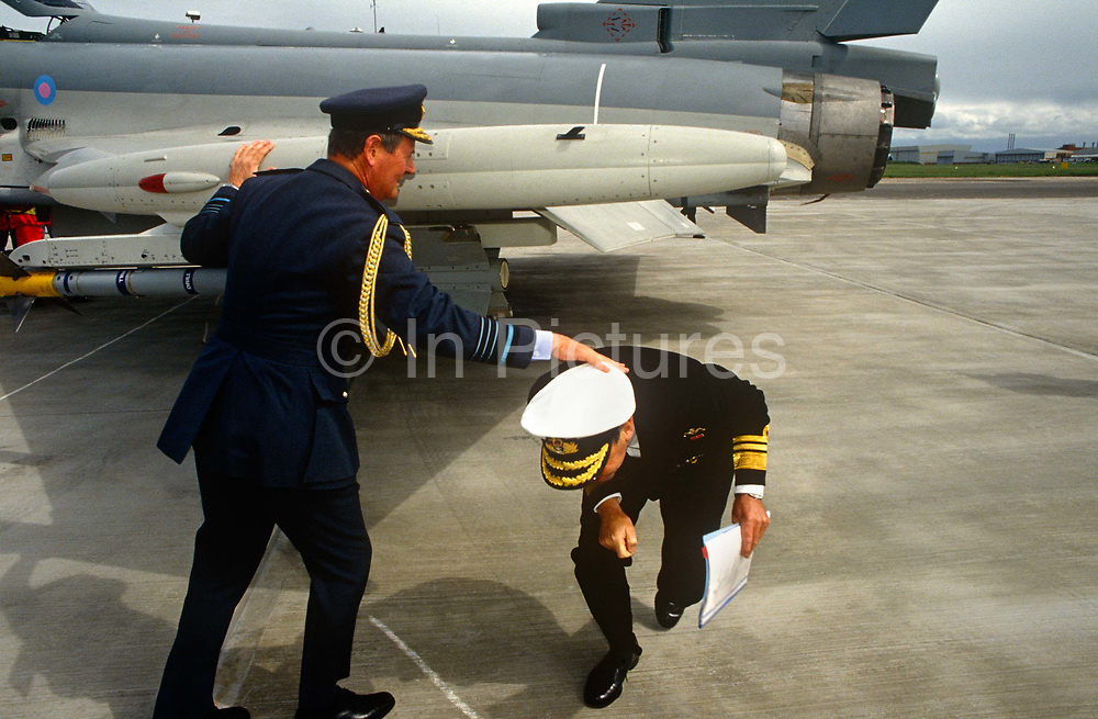 An RAF Air Chief Marshal helps a Royal Navy Vice Admiral just before he bangs his head under a new Eurofighter's (Typhoon) wing. It is the maiden flight of this now iconic jet fighter constructed by a consortium of European countries and manufacturers. The navy man is used to finding his way around a ship or low-ceiling submarine but obviously needs a helping hand while under the wing of this aircraft. The Royal Air Force officer wearing full dress uniform complete with gold braid holds the other's head on which rests his white Navy hat, also with gold insignia that denotes his senior rank. The Eurofighter Typhoon is a twin-engine, canard-delta wing, multirole combat aircraft, designed and built by a consortium of three companies. Its maiden flight took place on 27 March 1994 watched by VIPS from UK industry and military.