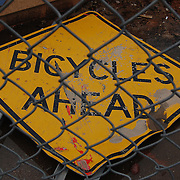 """""""Bicycles Ahead"""" road sign on ground behind chain link fence during Tucson's Interstate 10 widening project. Bike-tography by Martha Retallick."""