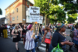 © Licensed to London News Pictures. 16/06/2017. London, UK. A demonstration and march by residents and campaigners arrives at Grenfell Tower in west London following a fire at the Grenfell tower block in west London earlier this week. The blaze engulfed the 27-storey building killing 12 - with 34 people still in hospital, 18 of whom are in critical condition. The fire brigade say that they don't expect to find anyone else alive. Photo credit: Ben Cawthra/LNP