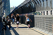 Two children (6 years old) skip past a kneeling photographer while crossing the Sydney Harbour Bridge. Sydney, Australia