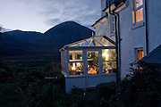 Barbara Christie sits reading in her conservatory of Swordale House overlooking Beinn Na Caillich nr Broadford, Isle of Skye.