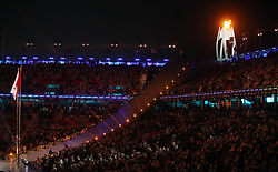 The Paralympic flame overlooks the Paralympic and Chinese flags during the Closing Ceremony for the PyeongChang 2018 Winter Paralympics in South Korea.