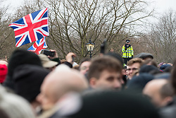 """© Licensed to London News Pictures . 18/03/2018 . London , UK . A policeman videos the crowd at Speakers Corner . 1000s including supports of alt-right groups such as Generation Identity and the Football Lads Alliance , at Speakers' Corner in Hyde Park where Tommy Robinson reads a speech by Generation Identity campaigner Martin Sellner . Along with Brittany Pettibone , Sellner was due to deliver the speech last week but the pair were arrested and detained by police when they arrived in the UK , forcing them to cancel an appearance at a UKIP """" Young Independence """" youth event , which in turn was reportedly cancelled amid security concerns . Photo credit: Joel Goodman/LNP"""