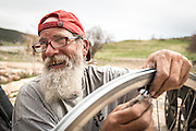 An inspiring man, Franklin, repairs a spoke on his bike as he rides across the country to visit his brother who is dying from cancer.