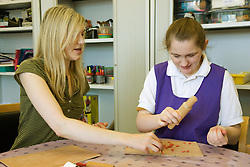 Day Care Assistant looking on as Service user with learning disability take part in an arts and crafts session,