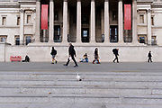 As passers-by hurry past, a busker plays his guitar to the public beneath the columns of the National Gallery in Trafalgar Square, on 14th October, 2021, in Westminster, London, England.
