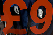 Trendy blue suits with red prices and lettering on display in a central London menswear shop. Part of the pricing has been cropped out of this picture - as, clearly, the suit is not worth just £9 - so the following zero is to the right.  The shop is on London's Oxford Street, an east to west road long known for clothing and low-cost fashion - and before that, for the route that condemned criminals would take towards the gallows at nearby Tyburn.