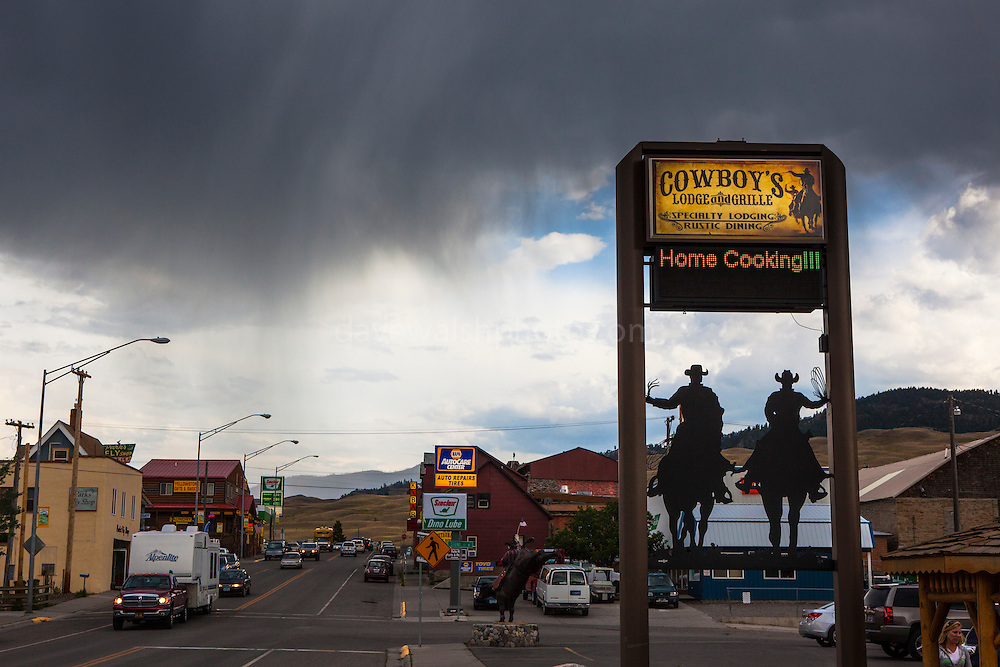 Restaurant sign at Cowboy's Lodge and Grille, Gardiner, Montana, the north west gateway town to Yellowstone National Park, with a rainstorm commencing in the background.